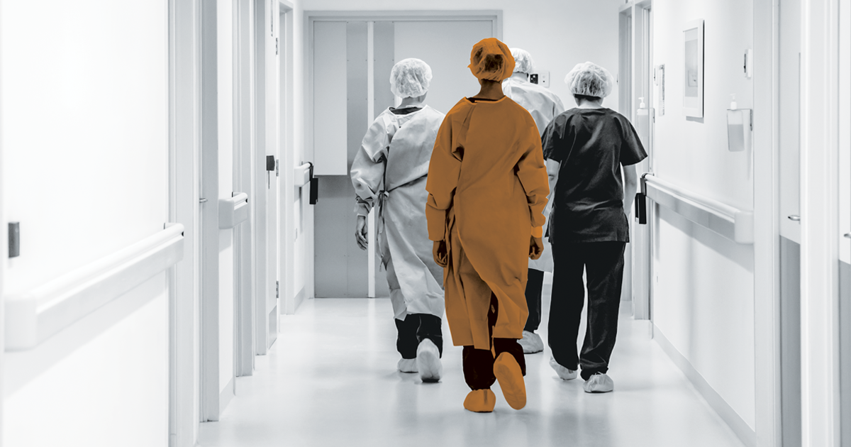 Image of NHS staff walking down a hospital corridoor.