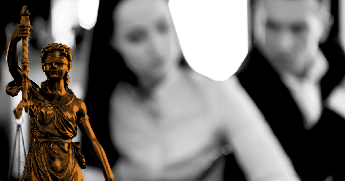 Image of Lady Justice in front of Two out of foucs figures.