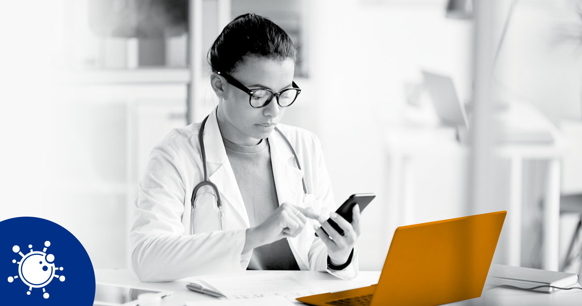 Image of a doctor using a smartphone whilst sitting at a laptop.
