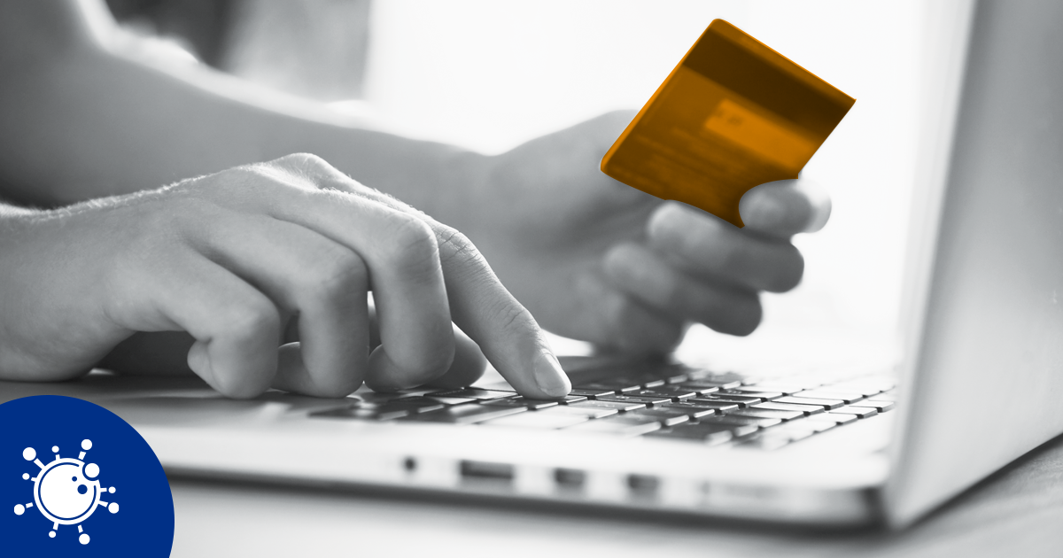Image of person holding a credit card whilst typing on a laptop