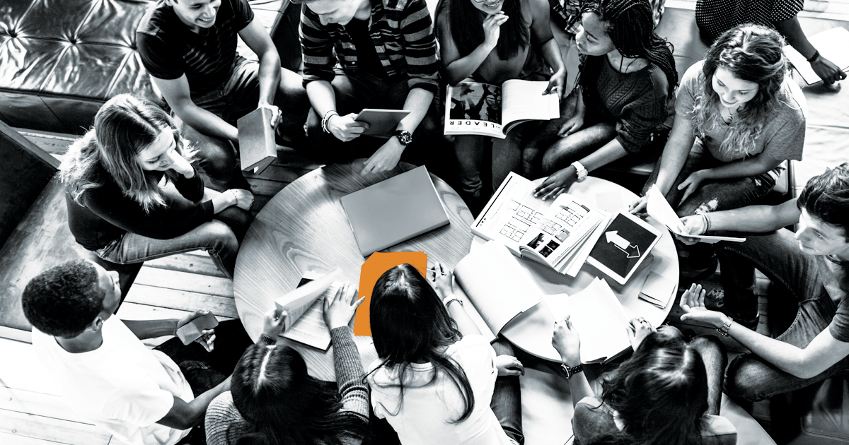 Image of a group of students studying with one document highlighted in oranges.